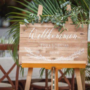 Willkommensschild aus Holz mit Kalligraphie in weißer Farbe