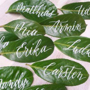 Blätter als Platzkarten mit moderner Kalligraphie in weißer Schrift