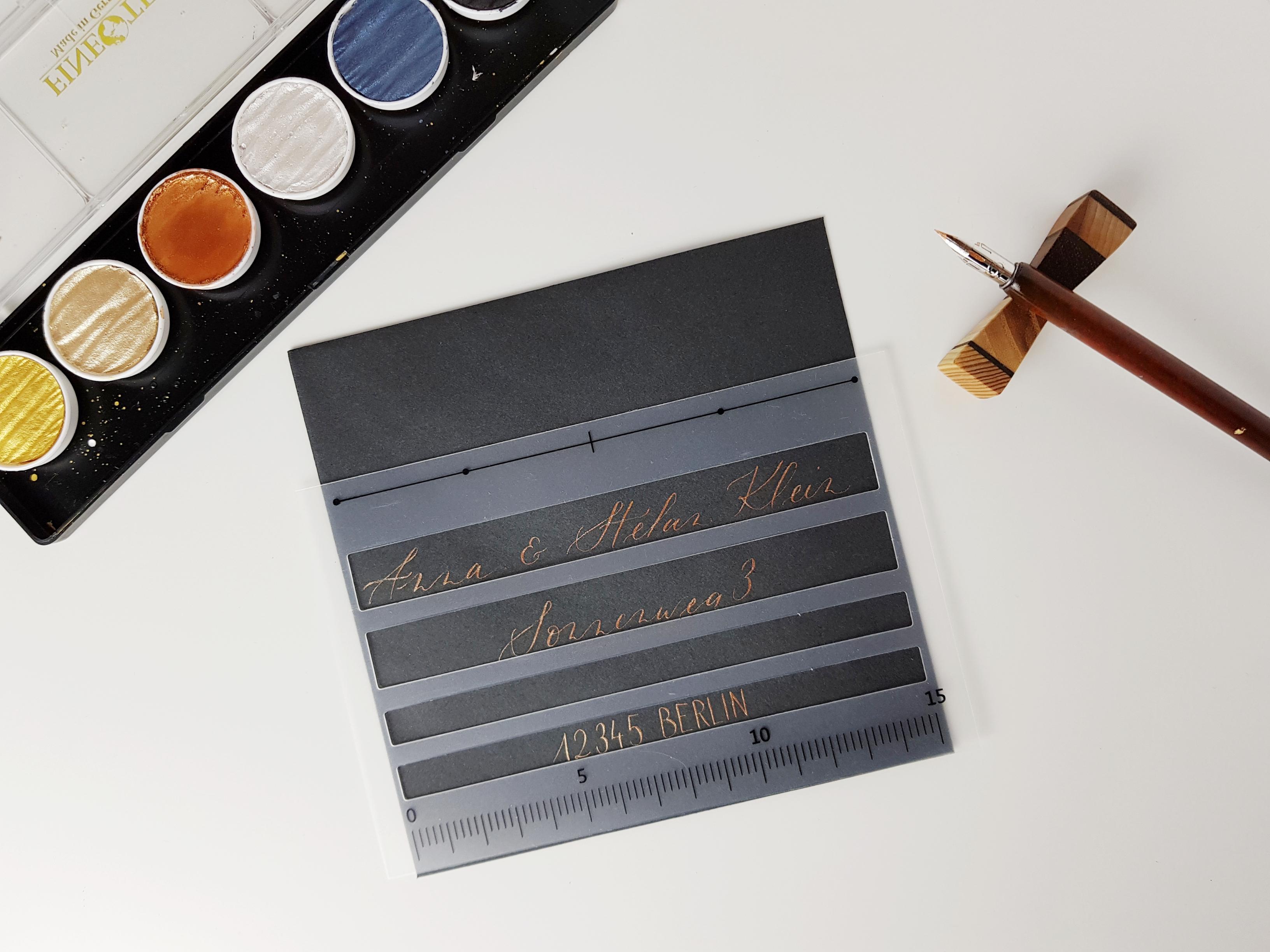 Beschriftung eines Umschlags mit moderner Kalligraphie mit Schablone als Hilfslinie