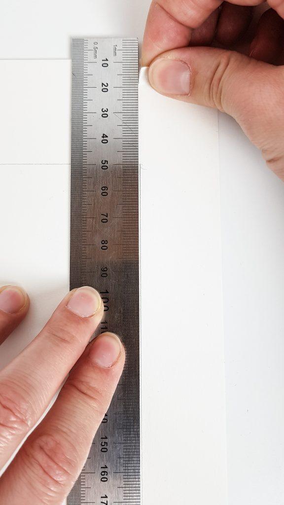 Das Papier direkt am Lineal greifen und nach unten reißen