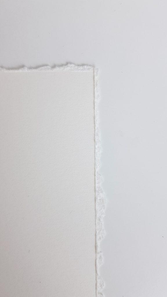 Auf der Vorderseite ist eine deutliche Kante vom Reißen am Metalllineal zu sehen