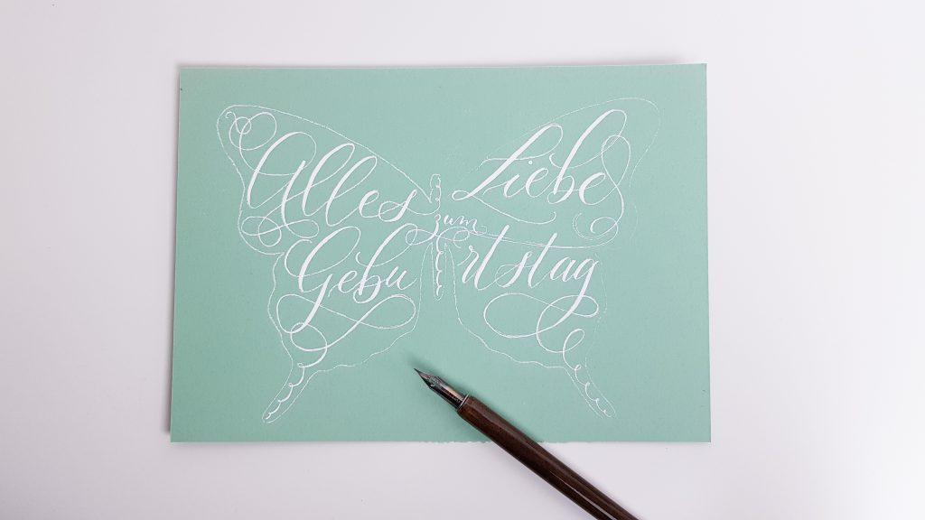 Kalligraphie der Geburtstagskarte wird mit weißer Tinte nachgezogen