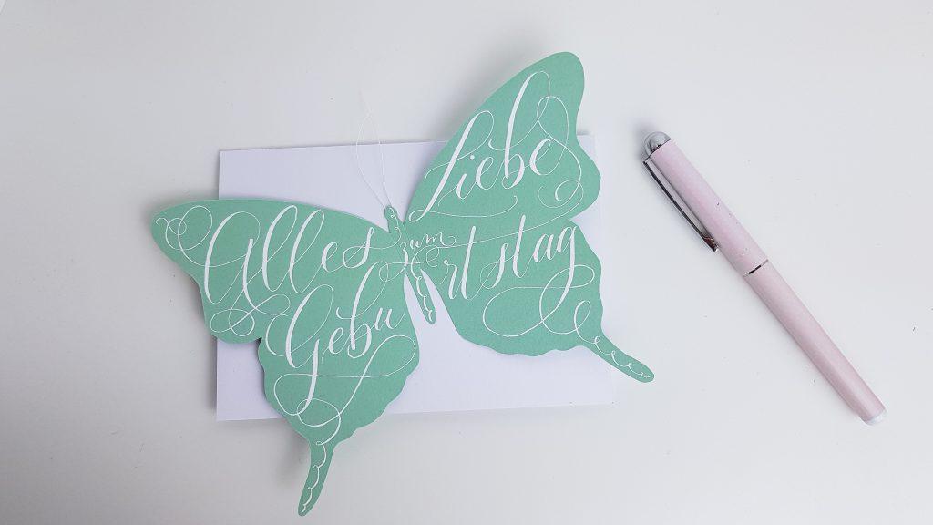 Schmetterling auf der weißen Geburtstagskarte festkleben